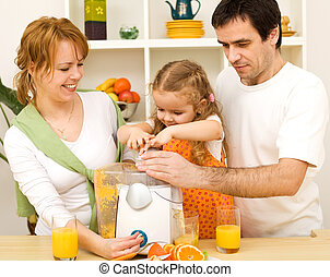 Family making fresh fruit juice together - Happy healthy...
