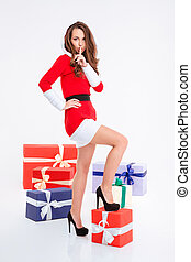 Woman in santa claus cloth showing finger over lips - Full...