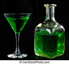 glass of cocktails - glass of green cocktails and bottle on...