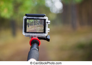 taking video with action camera on handheld stick