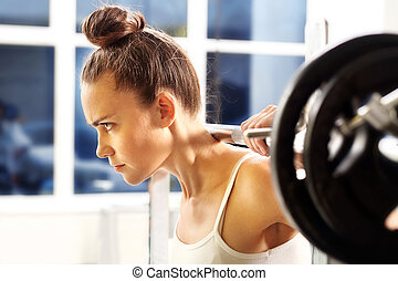 Weight lifting - The woman is picking barbell in gym