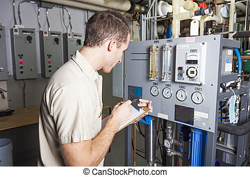Technician inspecting heating system in boiler room - A...