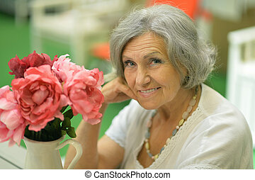 Older woman with flower - Portrait of a older woman with...