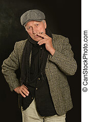 Senior man smoking cigarette over black background