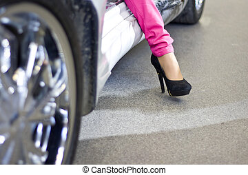 Celebrity woman exiting sportcar