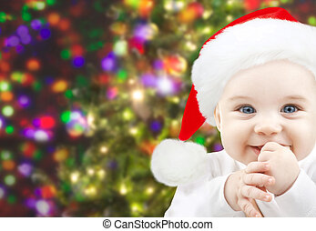 happy baby in santa hat over christmas lights - christmas,...
