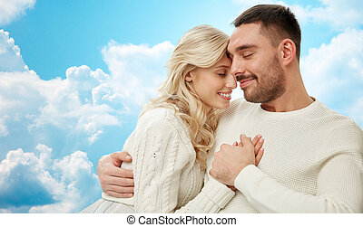 happy couple cuddling over blue sky and clouds