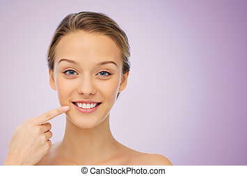 happy young woman pointing finger to her smile - beauty,...