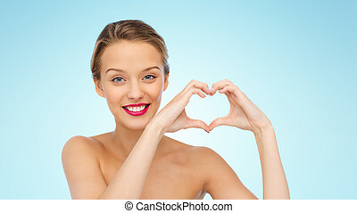 smiling young woman showing heart shape hand sign - beauty,...