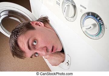 Surprised man inside washing machine - Close-up of surprised...