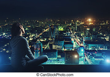 Pensive woman is looking at night city - Pensive woman is...