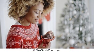 Young woman enjoying a Christmas treat sitting in front of a...