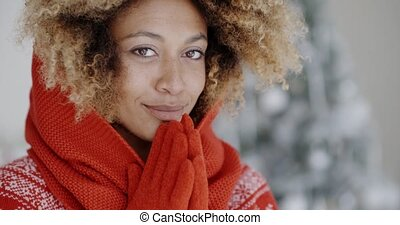 Cute young African woman in winter fashion wearing a festive...