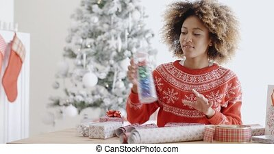 Attractive young woman wrapping Christmas gifts - Attractive...