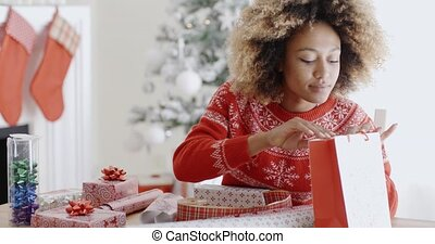 Pretty young woman wrapping Xmas presents - Pretty young...