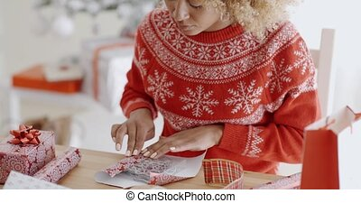 Young woman carefully wrapping a Christmas gift in a...