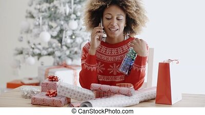 Woman chatting on a mobile as she wraps gifts - Young...