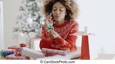 Woman chatting on a mobile as she wraps gifts