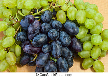 grapes - On the table are ripe bunches of white and black...