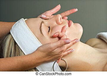 Facial treatment - Hands giving a young woman a facial...