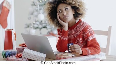 Young woman pondering over an online purchase holding her...