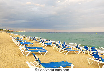 deckchairs on a pebbled beach, facing out to sea