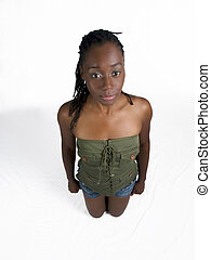Young black woman kneeling in shorts and green top