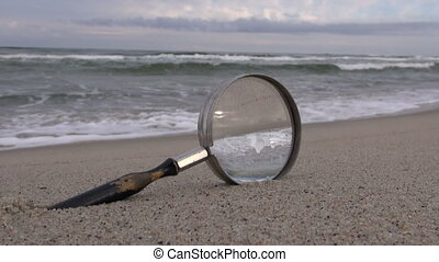 Vintage magnifying glass on beach - Antique magnifying glass...