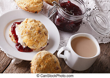 Homemade scones with jam and tea with milk close-up....