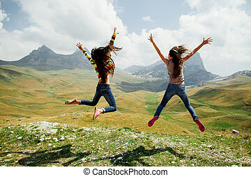 two girls happy jump in mountains with exciting view - two...