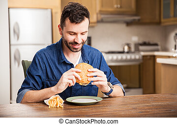 Man eating a burger at home