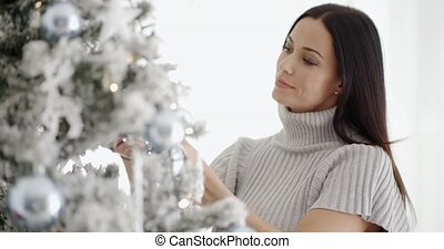 Pretty young woman decorating her Christmas tree - Pretty...