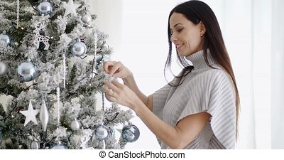 Pretty trendy woman decorating an Xmas tree placing...