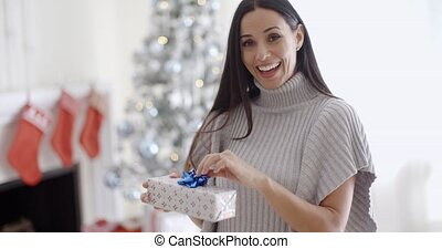 Smiling young woman opening a Christmas present - Smiling...