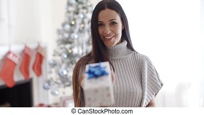 Smiling young woman holding out a Christmas gift - Smiling...