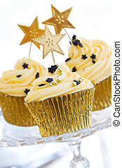 Golden cupcakes - Three golden cupcakes on a glass cake...
