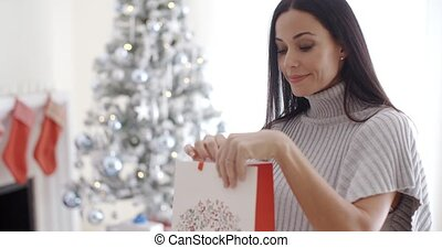 Young woman opening a Christmas gift bag to peer inside with...