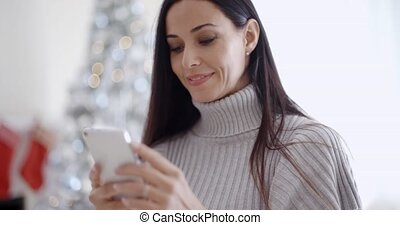 Attractive young woman reading a text message on her mobile...