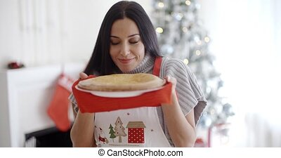 Attractive young woman baking tarts for Xmas standing in...
