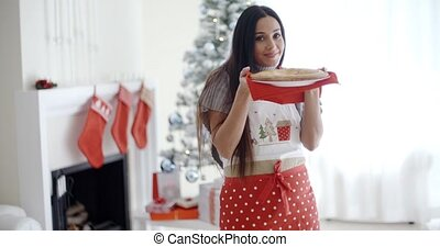 Smiling laughing young Christmas cook in a festive red apron...