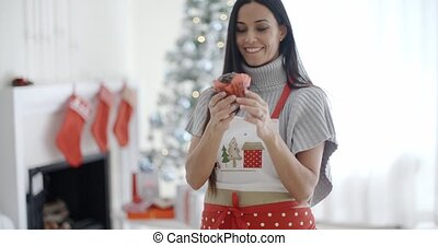 Pretty young woman enjoying her Christmas baking standing in...
