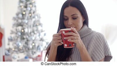 Woman enjoying a cup of Christmas coffee - Attractive young...