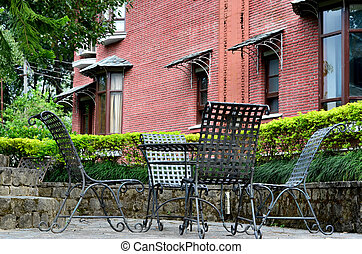 Chairs in a hedged area with brick wall - Chairs placed in a...