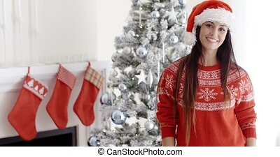 Pretty young woman celebrating Christmas at home posing in...