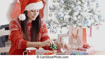 Young woman decorating her Christmas gifts with bows and...