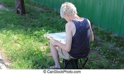 Boy making sketches - Boy in black t-shirt do drawing