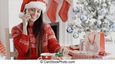Young woman making a Christmas greeting call - Young woman...