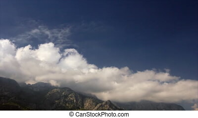 Mountains in clouds - Billowing clouds on the rocks of the...
