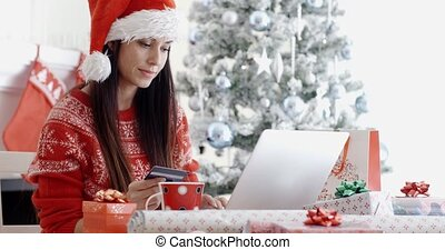 Young woman ordering Christmas gifts online - Young woman in...