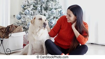 Young woman and her dog celebrating Christmas - Young woman...